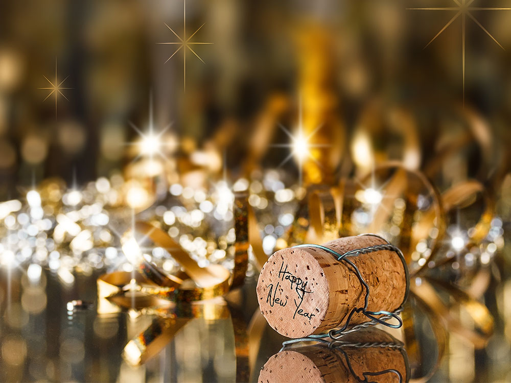 Wine cork with Happy New Year written on top and glittering in the backdrop