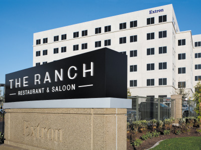The outside view of THE RANCH Restaurant & Saloon street signs and 6 story Extron building.