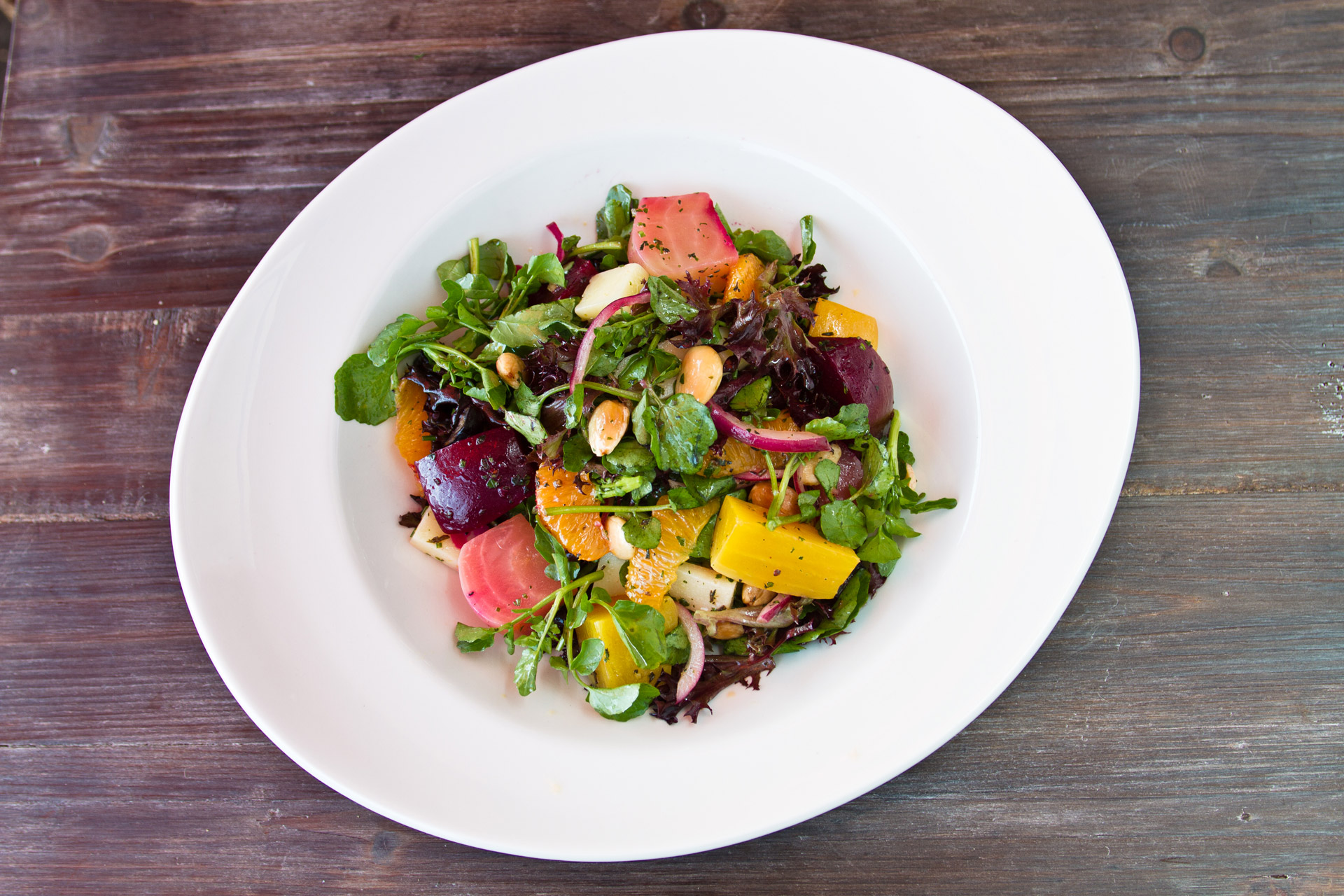 Green leaves with beets, oranges, purple onions, and almonds