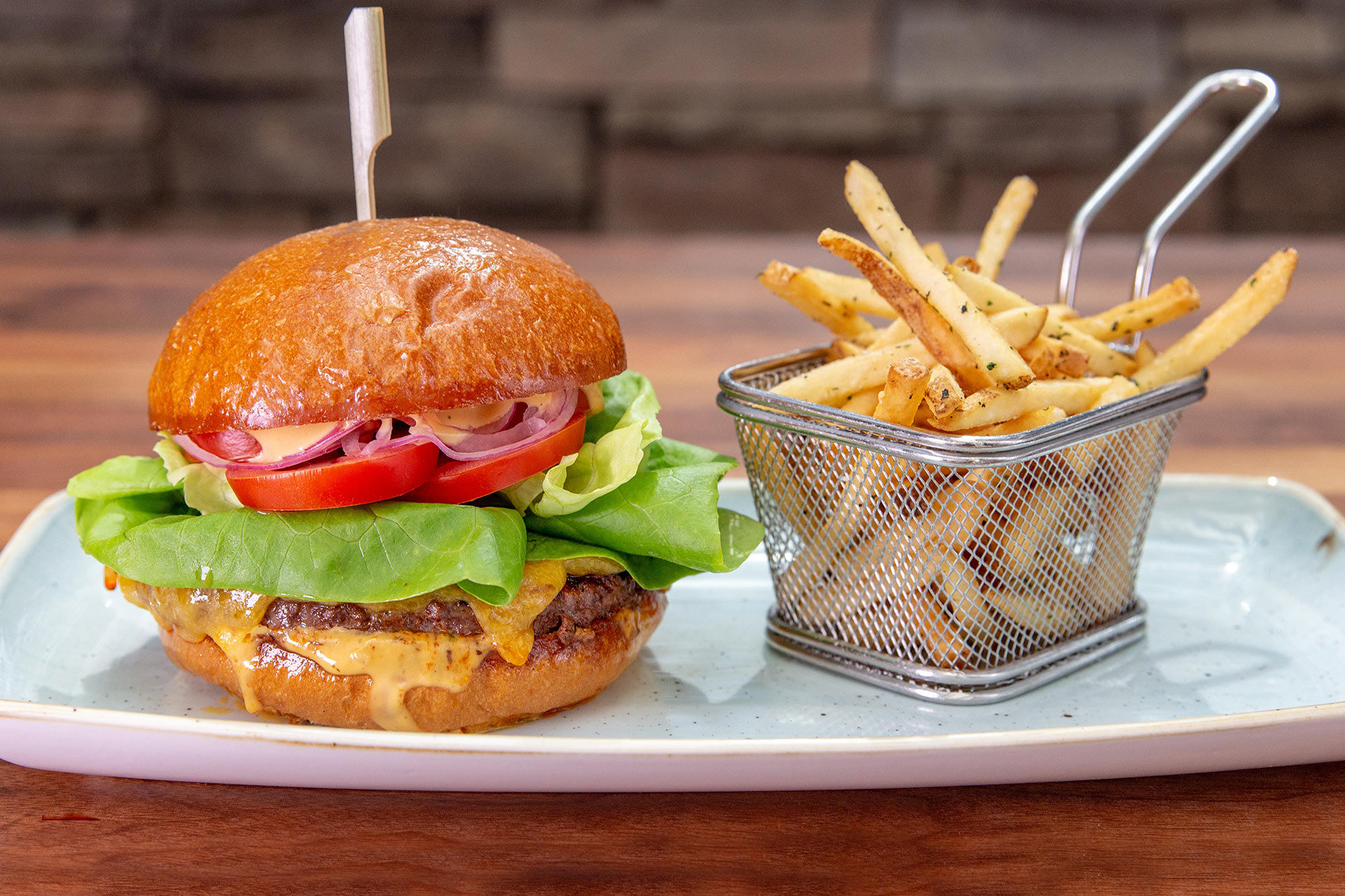 Juicy steak burger piled high with all the fixings, a basket of crispy french fries, and a fresh dill pickle half.