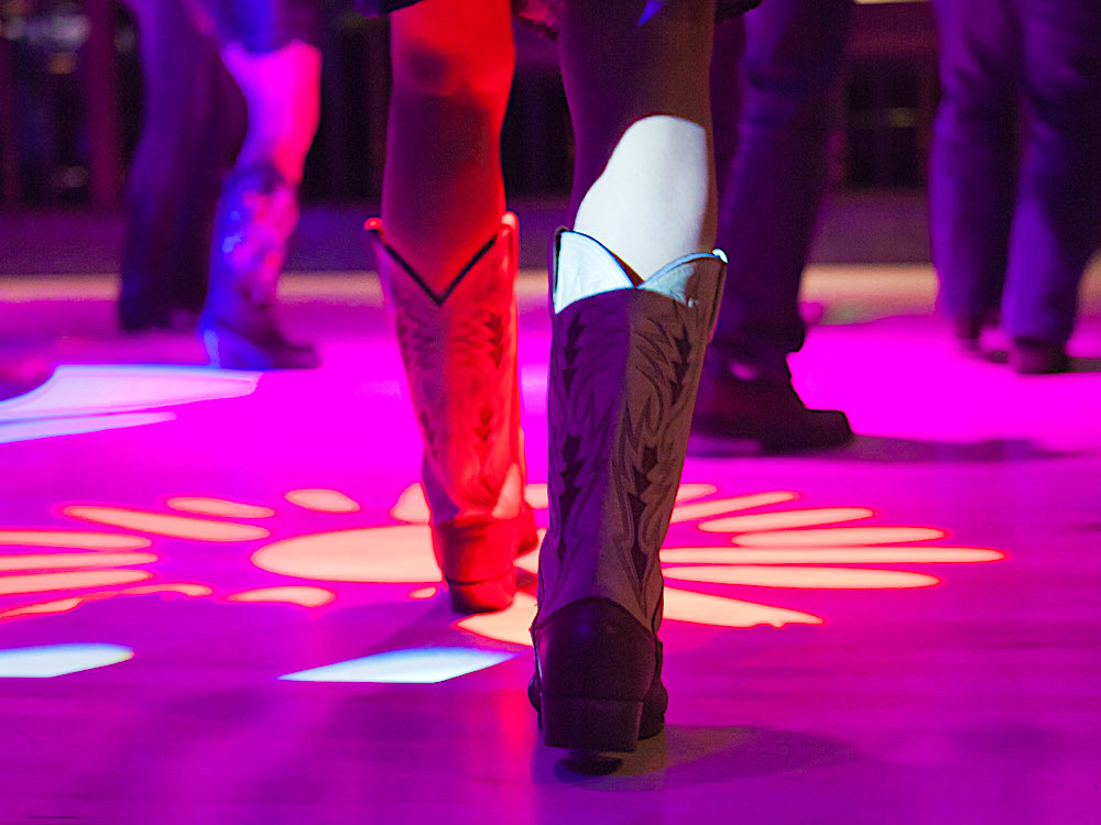 Close-up view of cowboy boots and types of footwear allowed on the dance floor for dancing and live music performances.