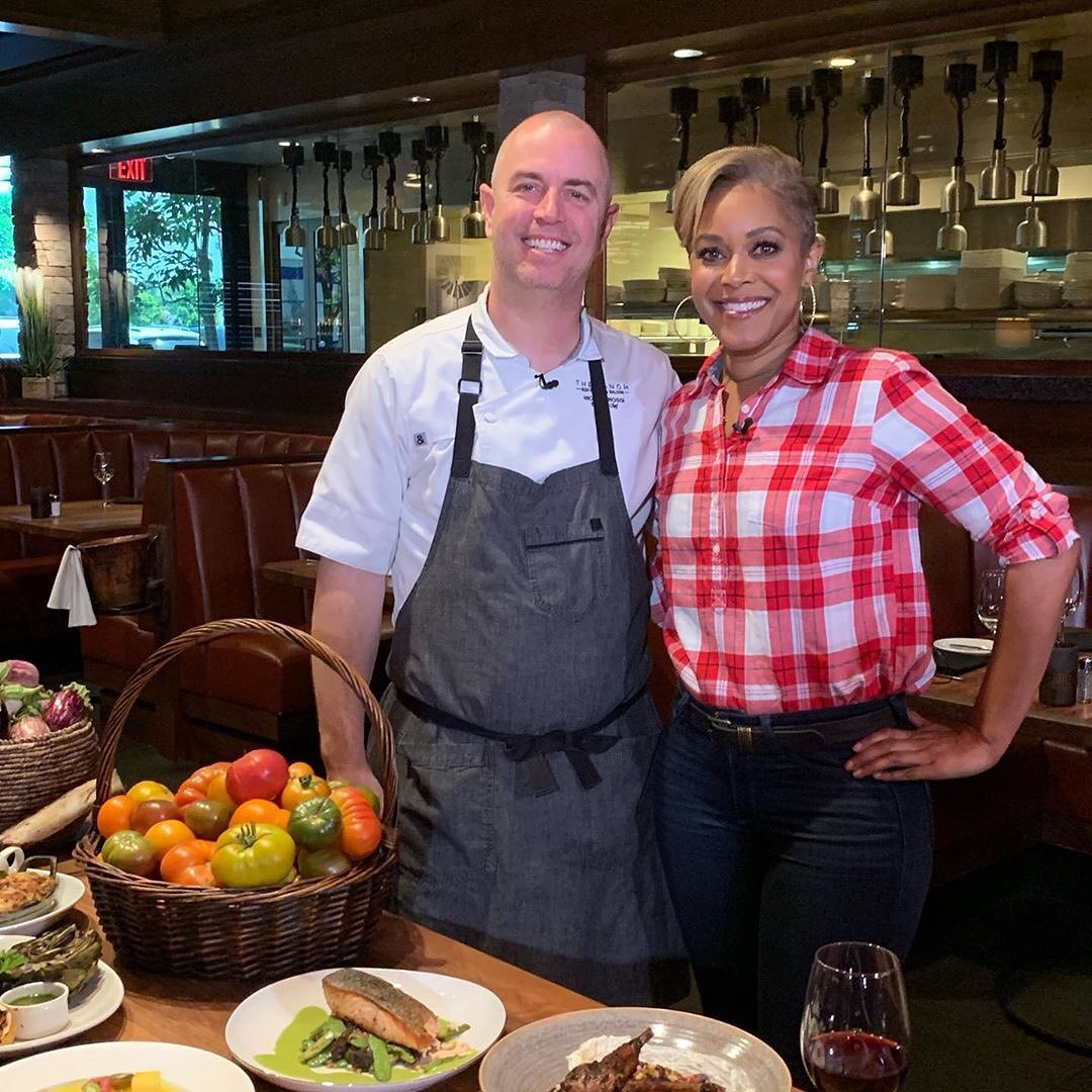 Chef standing with a TV reporter and a table of food.