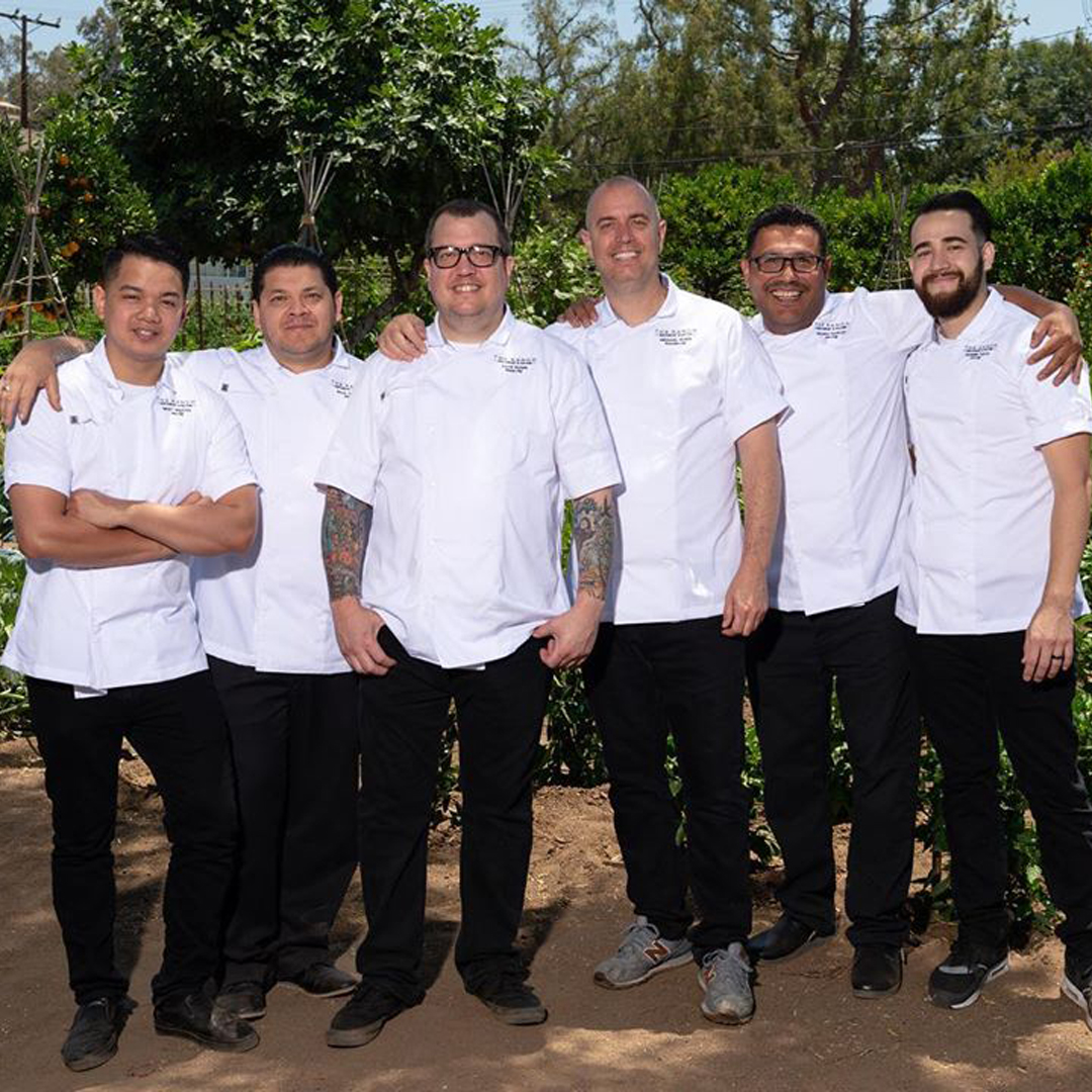 A team of chefs standing in front of a farm.