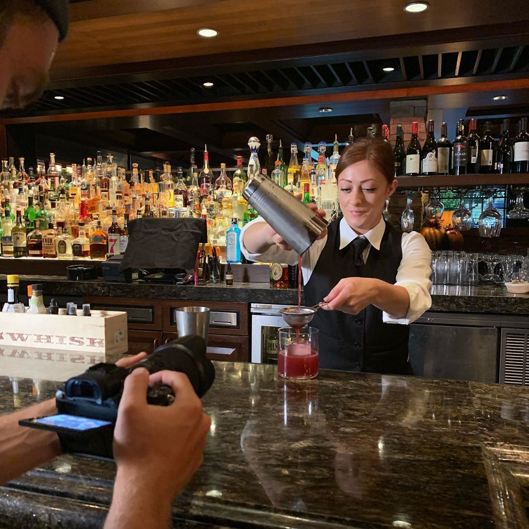 A photographer shooting a bartender pouring a drink.