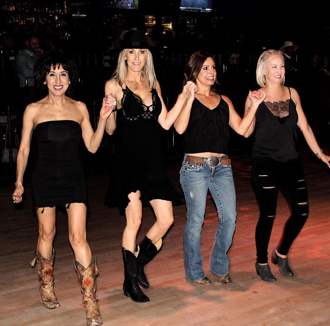 A group of 4 women dressed in all black dancing around a dance floor.