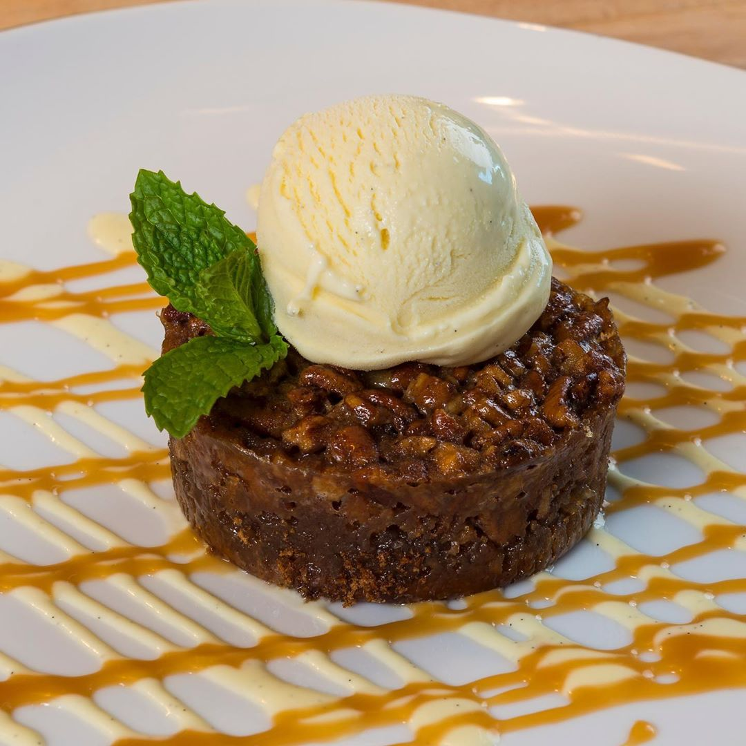 A nutty dessert with ice cream on top and a caramel drizzle.