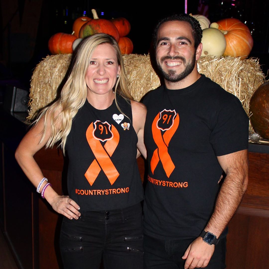 A couple wearing black and orange shirts in front of a stage.
