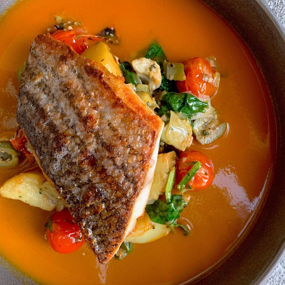 Baja Striped Bass dish with brightly colored vegetables and sauce.