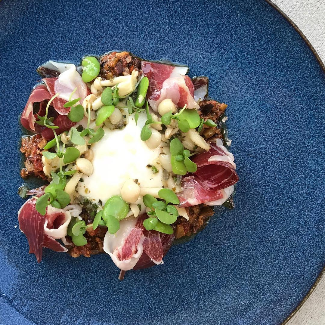 Blue plate with burrata, Jamón Ibérico Americano, Olives, Clamshell Mushrooms, and Fava Beans.