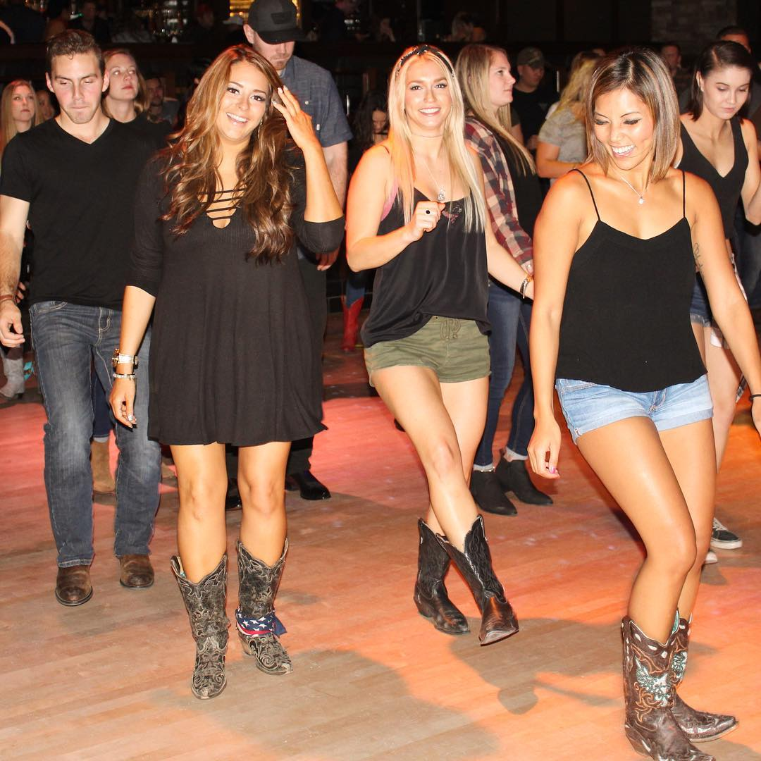 Group of line dancers on dance floor.
