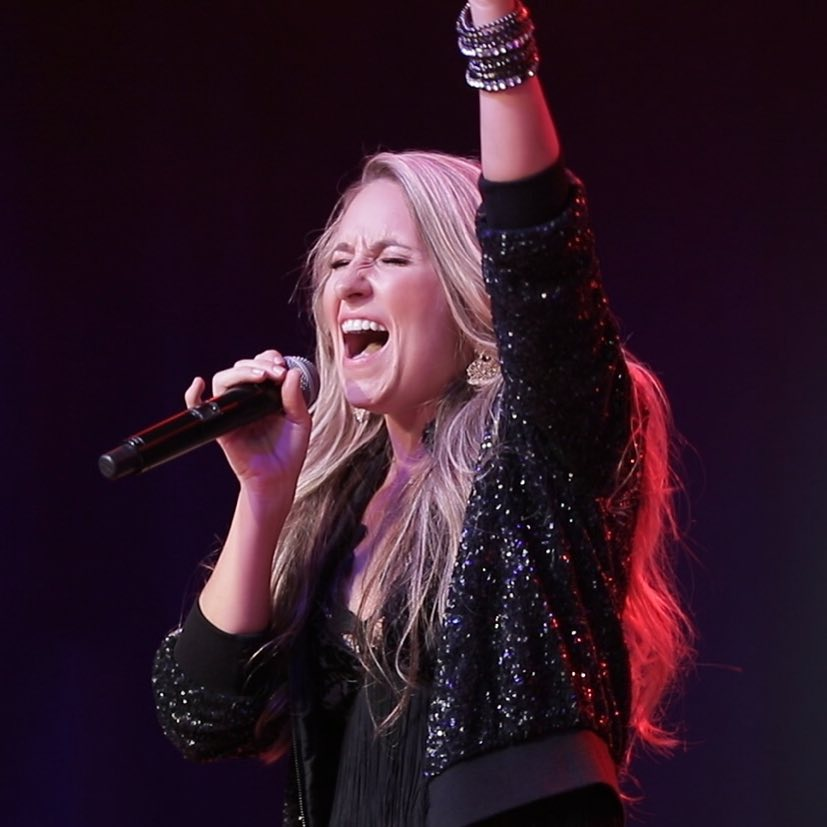 Female singer with microphone in hand, wearing a black glitter jacket.
