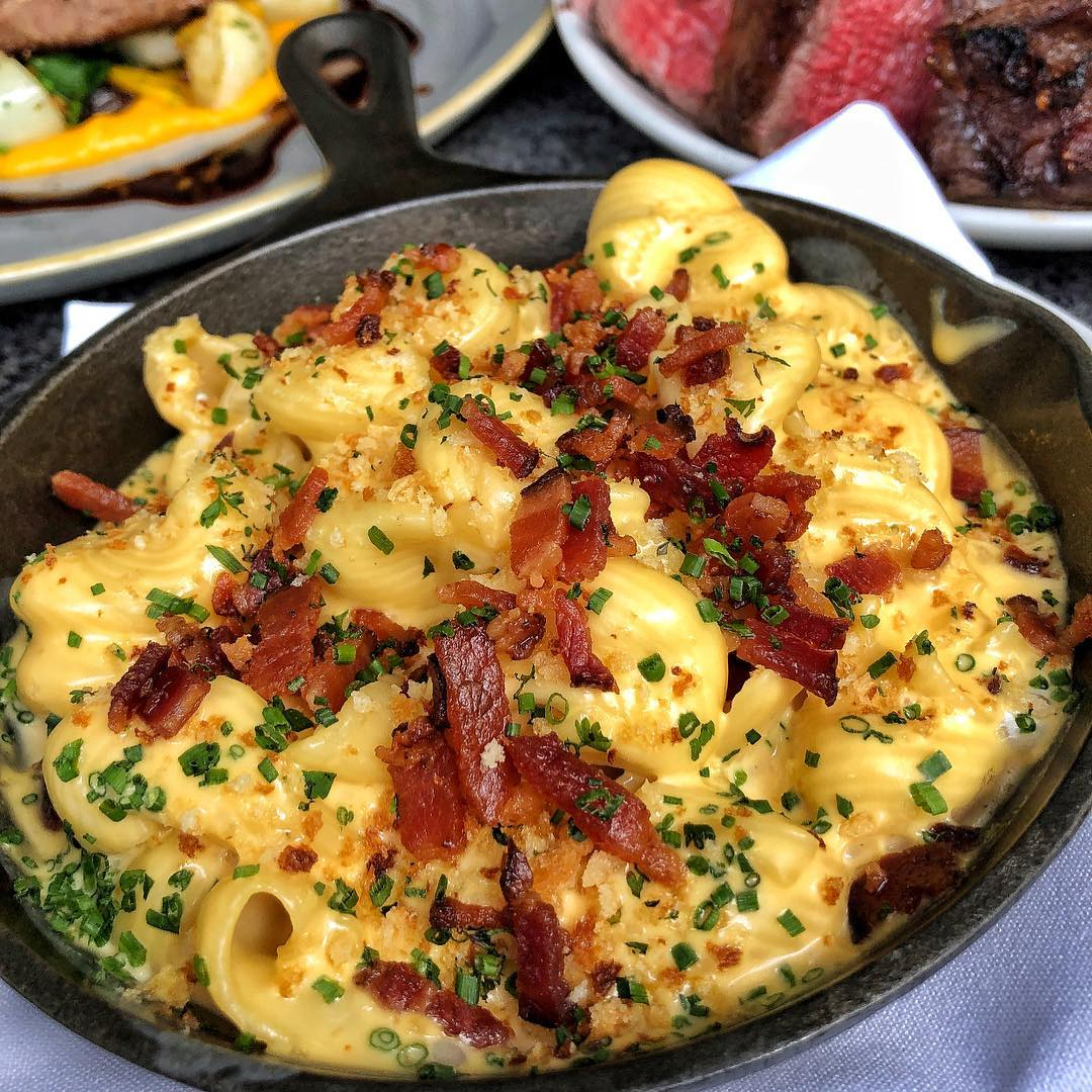 Cast iron skillet with macaroni and cheese topped with bacon and chives.