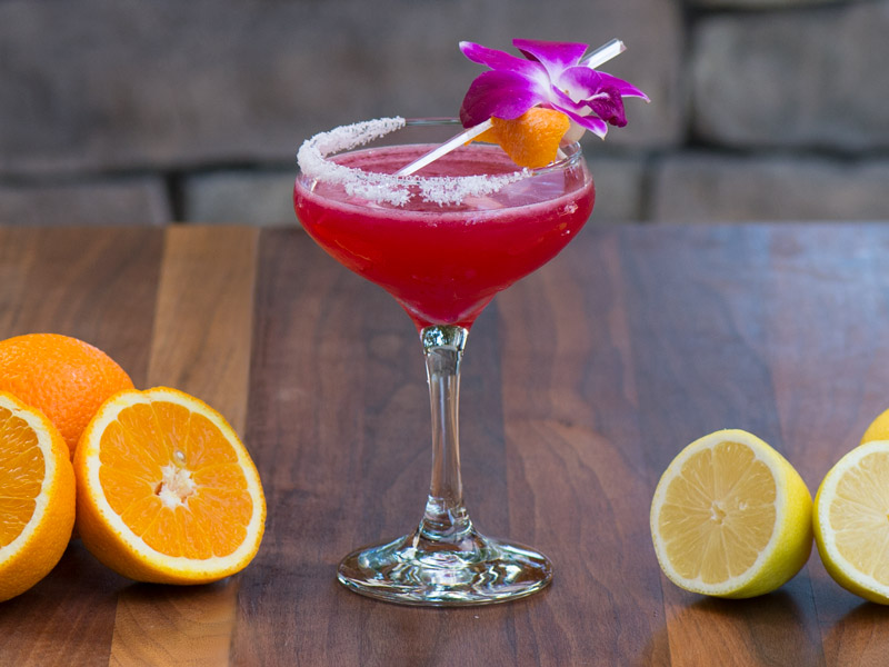 Bright red cocktail in a sugar-rimmed stemmed glass with an orchid plus cut oranges and lemons to either side.