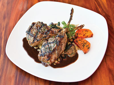 White dinner plate with grilled lamb chops, mushrooms, and tomatoes served with sprigs of mint and a rich brown sauce.
