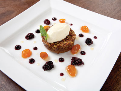Dessert of old-fashioned pecan pie with freshly whipped cream, golden currents, and plump berries.