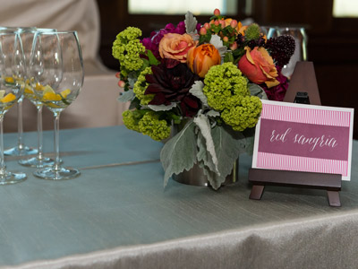 Elegant table setting with stemmed glassware, a rose and floral bouquet in a glass vase, and a personalized place card.