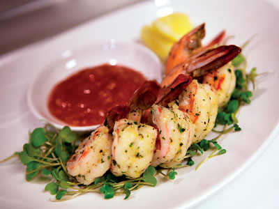 White plate of grilled shrimp on a bed of parsley and a lemon wedge arranged around a dish of red cocktail sauce.