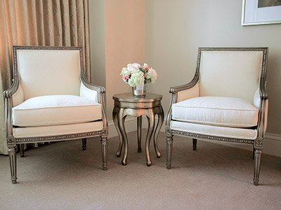 Two white chairs on either side of a silver end table holding flowers.