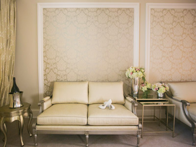 A wall of the Bridal Suite, with a pair of the bride's heels on a creme sofa.
