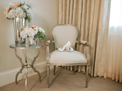 A lounge chair with a pair of the bride's heels on them, next to a a glass table with floral arrangements.