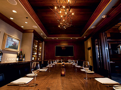 The Carolina Room, featuring with a long dining table, chandelier, built-in wine cabinets, counter, and tv monitor.