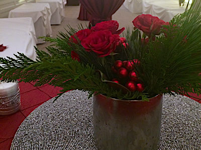 A round table with red and green flowers and a candle on it.
