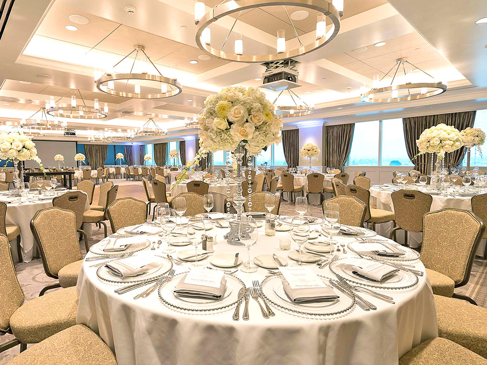 The Great Room with round tables set with large flower centerpieces, a dance floor, and chandeliers.