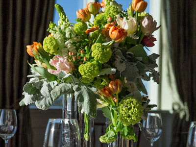 A green, white, and orange floral arrangement with glassware in front of windows.