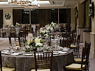 The Great Room set up with grey dining tables and green and white flowers.