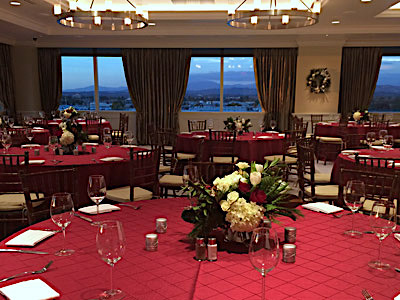 The Great Room set up with red dining tables and red and white flowers.