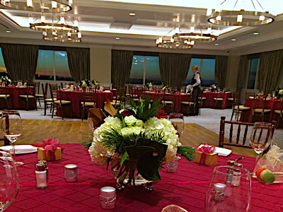 The Great Room set up with red dining tables and red and white flowers, and a dance floor.