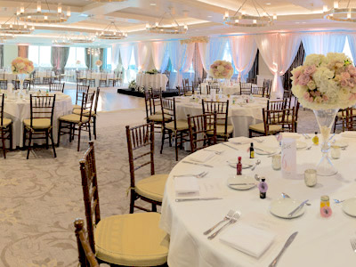 A wideshot of The Great Room set up for a wedding with wooden chairs and rose bouquet centerpieces.