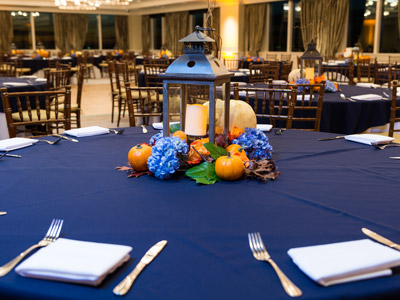 A closeup of a round table and a centerpiece consisting of a lantern and tiny pumpkins and lilacs.