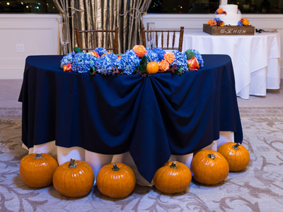 The bride and groom's table, showing the lilac and orange rose decorations, and pumpkin decor.