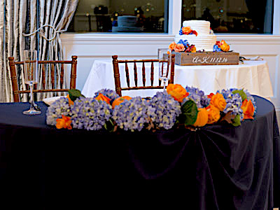 A closeup of the bride and groom's table, decorated with lilacs, orange roses, and tiny pumpkins.