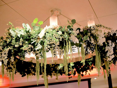 A chandelier with white and green flowers decorating it.