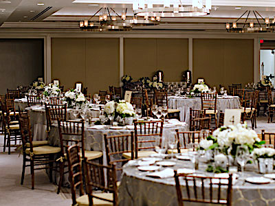The Great Room set up with grey dining tables and green and white flowers, and a buffet table.