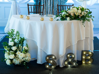 The bride and groom's table, decorated with flowers, candles, and lights of the couples' initials.