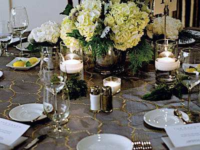 A round table set with glassware and flatware, green and white flowers, and candles.
