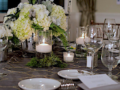 A closeup of a round table set with glassware and flatware, green and white flowers, and candles.