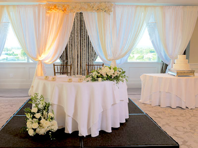 A front view of the bride and groom's table decorated with white roses and the wedding cake table.