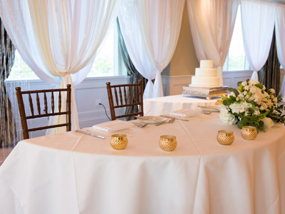A close up of the bride and groom's table, with candles and white rose decorations.