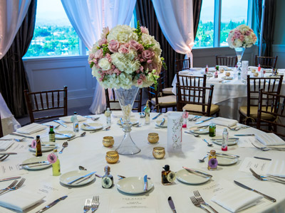 A close up of a guest table with a rose bouquet centerpiece, candles, and small guest favors.