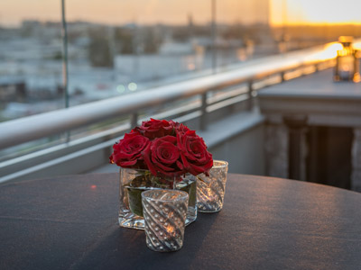 Closeup of a beautiful red flower and votive candles on The Terrace.