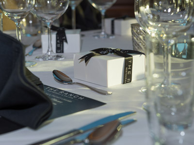 A closeup of a table setting with glassware, flatware, black menu, napkin, and gift boxes.