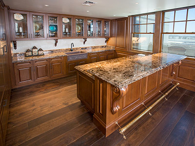 The Hospitality Suite kitchen area with built in cabinets, granite countertops, and bar.
