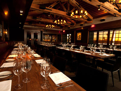 Long dining space with two, dark wood tables, beamed ceiling, chandeliers, and a built-in bar at the far end.