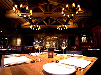 A room with wooden paneling, chandeliers, and looking at a wooden table.