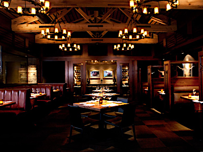 A large room with wooden paneling, chandeliers, private dining room, and wooden tables.