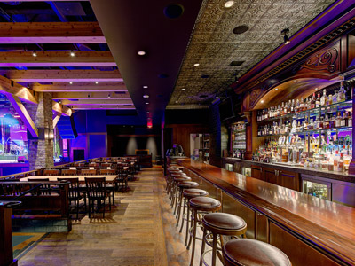 A bar with stools, next to wooden tables and chairs overlooking a dance floor and stage